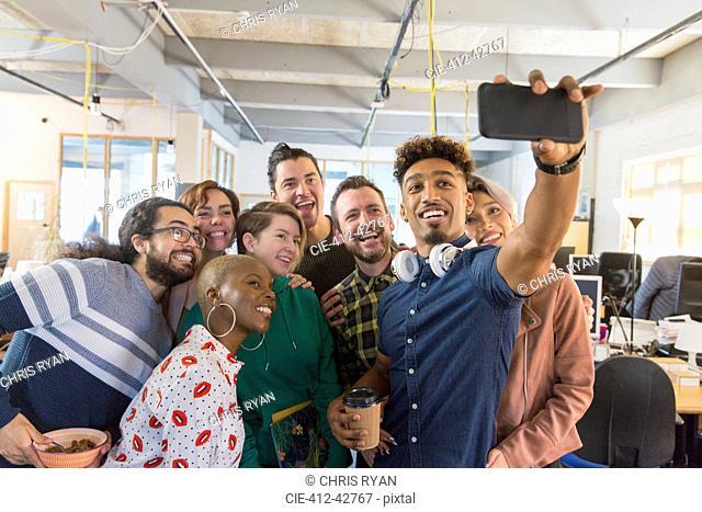 Creative business team taking selfie in office