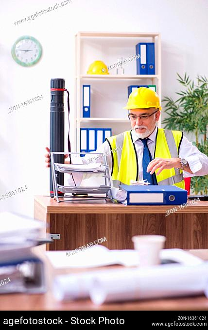Old male architect working in office