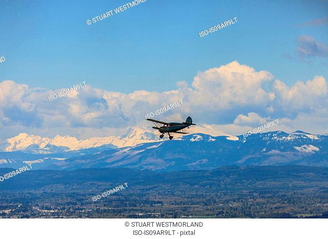 Silhouetted bi-plane flying above snow capped mountainous landscape