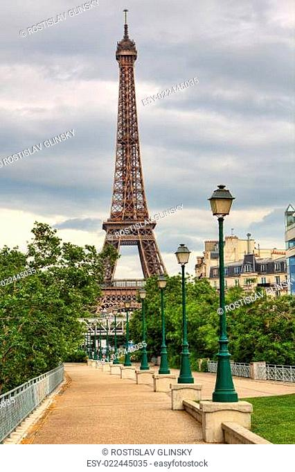 Vertical oriented image of famous Eiffel Tower and traditional urban lampposts in Paris, France
