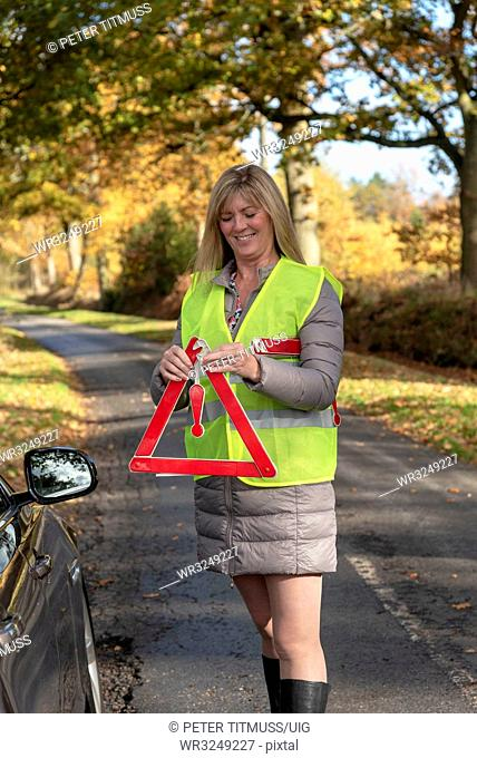 Female motorist putting out a reflective safety triangle following a roadside breakdown