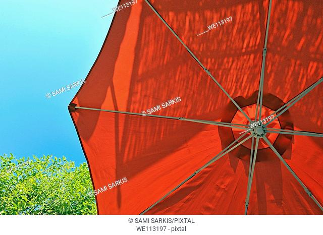 Reddish umbrella against blue sky, by trees in Provence, France