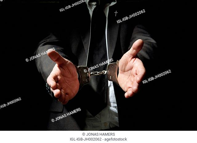 Picture shows a Handcuffed businessman on a black background