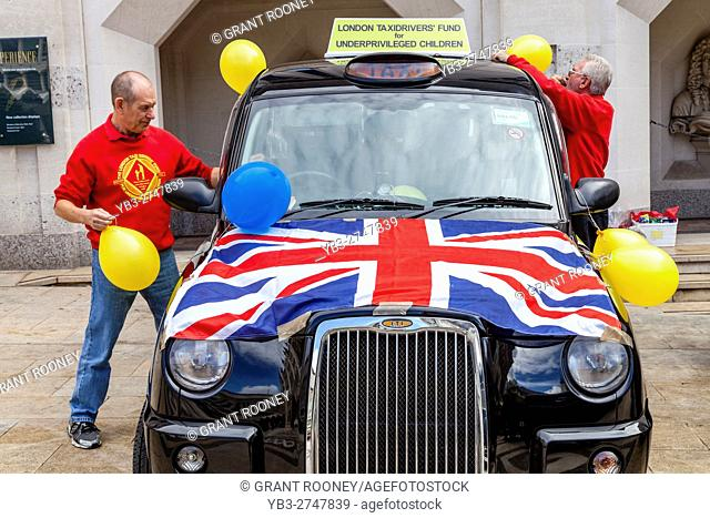 A Black London Taxi and Driver Take Part In The Pearly Kings and Queens' Harvest Festival Event For A Childrens Charity, The Guildhall Yard, London, England