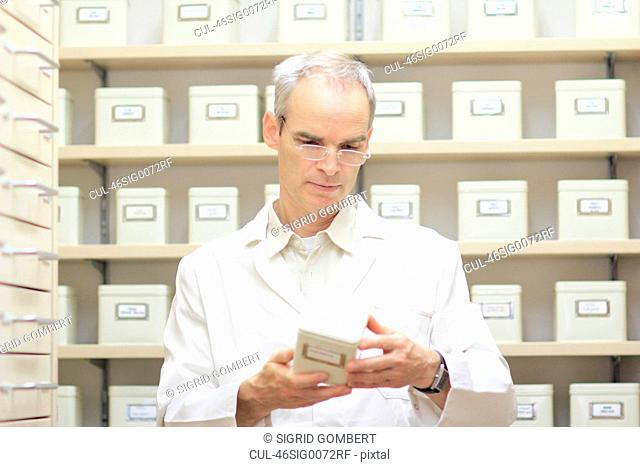 Pharmacist examining box of pills