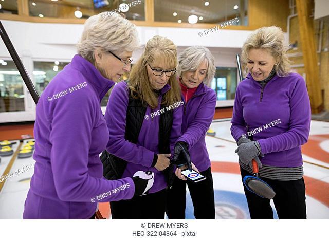 Senior women curling team scoring with mobile app on smart phone