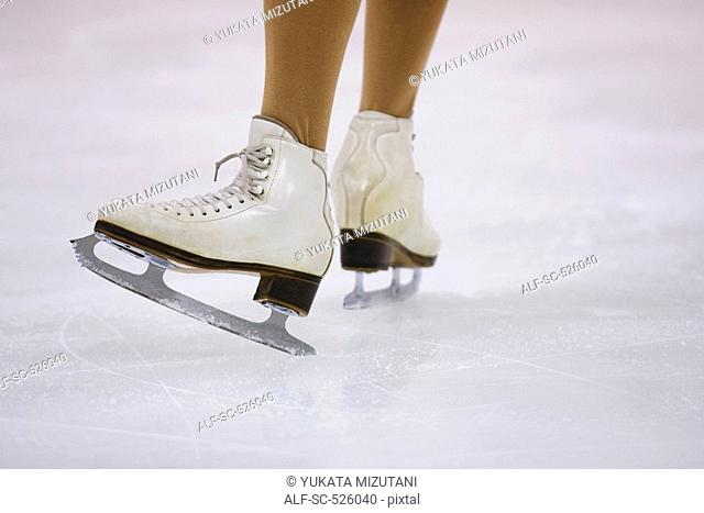 Legs of an skater skating with white ice skates