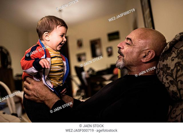 Happy grandfather playing with his grandson at home