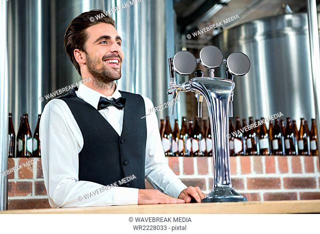 Handsome barman smiling next to the tap