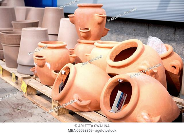 Many clay flowerpots on wooden pallets in market, decorative garden accessories on the ground in market place in shop outside, nobody
