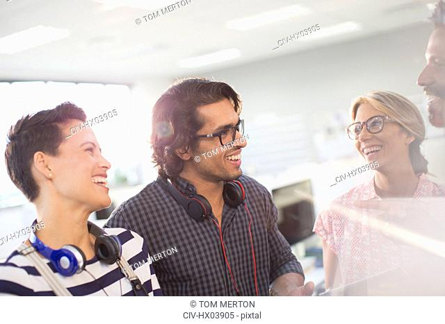 Smiling creative business people talking in office