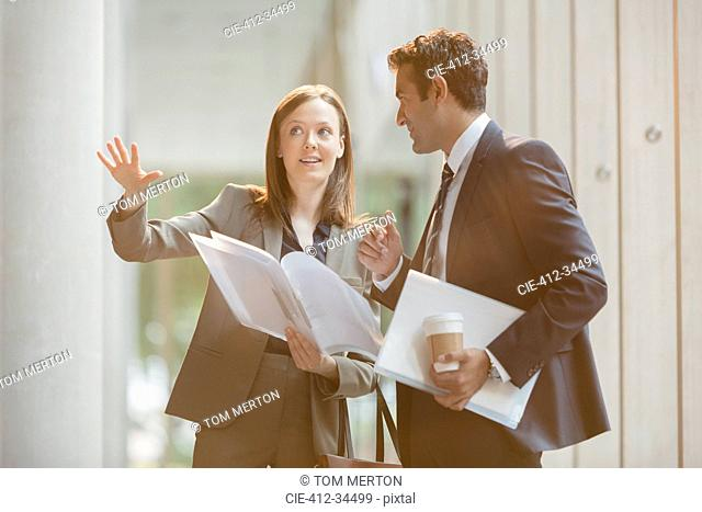 Businesswoman explaining paperwork to businessman in office lobby
