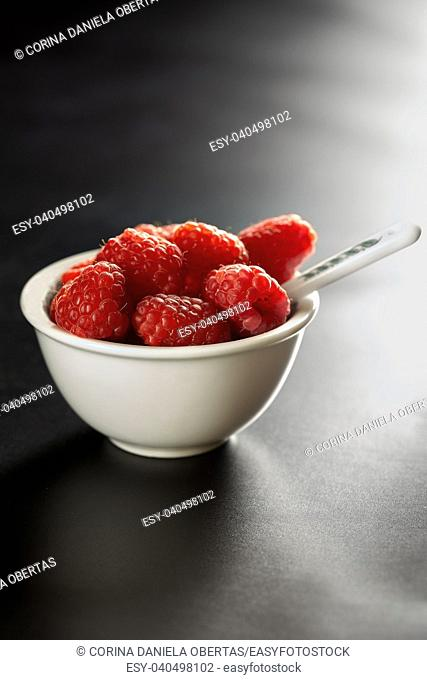 Bowl with fresh raspberries in backlight on black background
