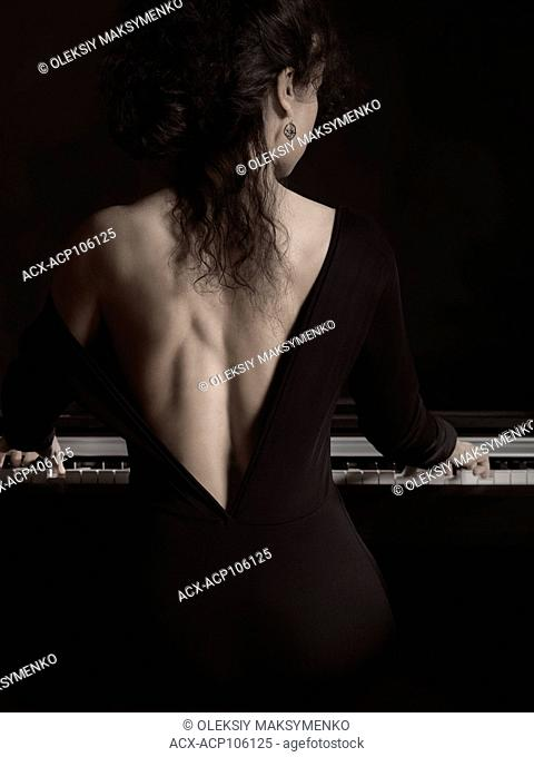 Sensual artistic portrait of a beautiful woman in a black dress with a revealing low back cut playing the piano