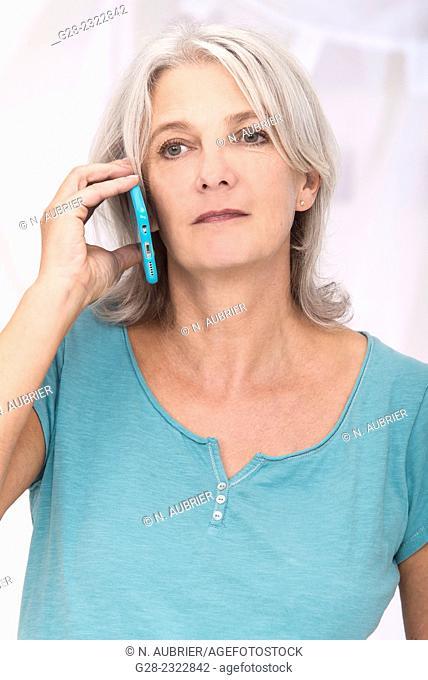 Beautiful mature woman using a blue i-phone