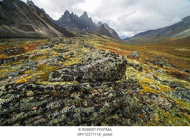 The Tombstone Valley in autumn colours with Tombstone Mountain rising above the tundra in Tombstone Territorial Park; Yukon, Canada