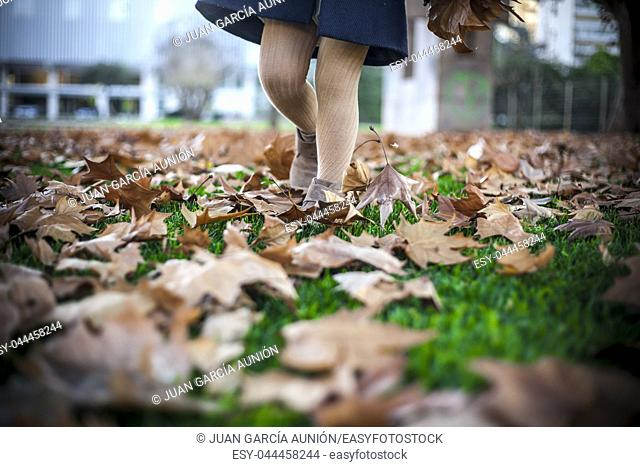 Child girl walking over fallen leaves carpet at park. Autumn and kids concept