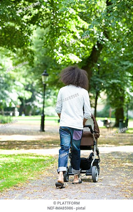 Rear view of young man pushing baby carriage in park