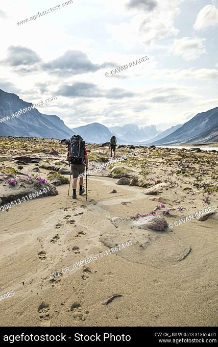 Rear view of two backpackers hiking, leaving footprints in the sand