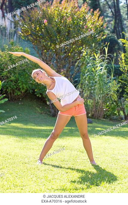 Woman practicing exercise in park, summertime