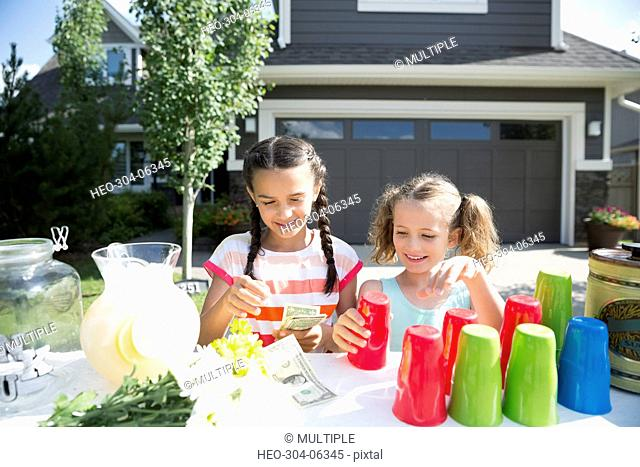 Girls counting money at sunny lemonade stand in driveway