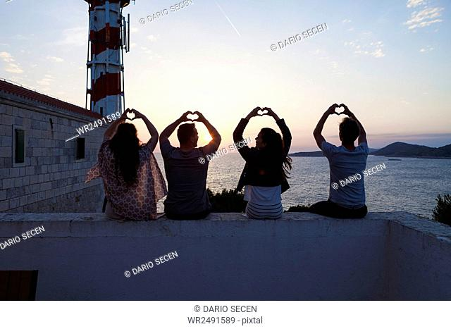 Young people making heart shapes with hands at the seaside