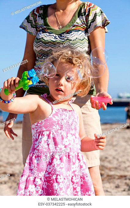Having fun with bubbles on a beach on sunny day