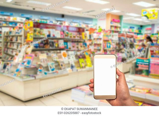 Smart phone white screen in hand on blurred book shop background