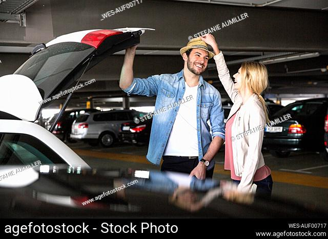 Young woman putting trilby on boyfriend's head in airport parking lot