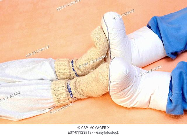 Two Couple's feet warming at a bed