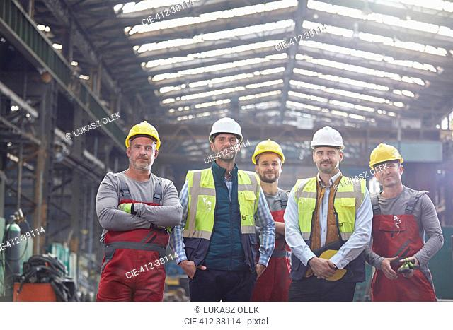 Portrait confident engineers and workers in factory