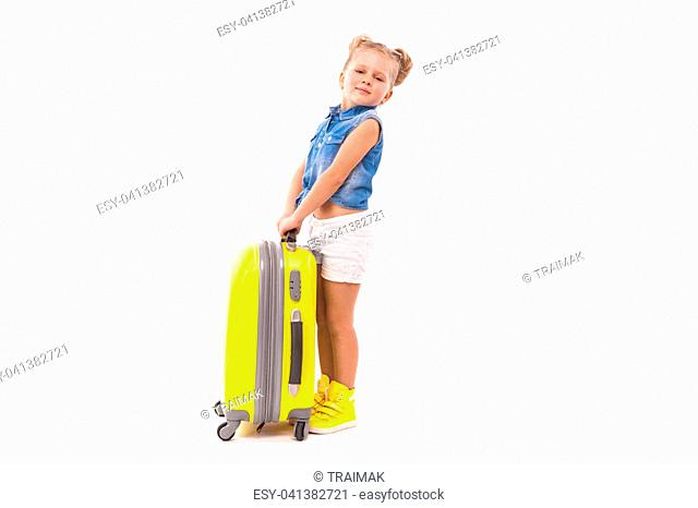 Isolated on white, beauty caucasian blonde girl in blue shirt, white shorts, sunglasses and yellow boots stand near yellow suitcase, hands on handle