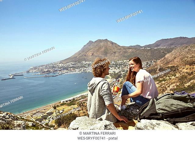 South Africa, Cape Town, smiling young couple sitting at the coast