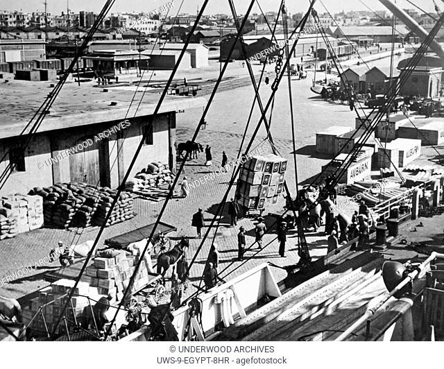 Alexandria, Egypt: c. 1930 A view of the cargo and shipping industry at the docks in the Alexandria harbor