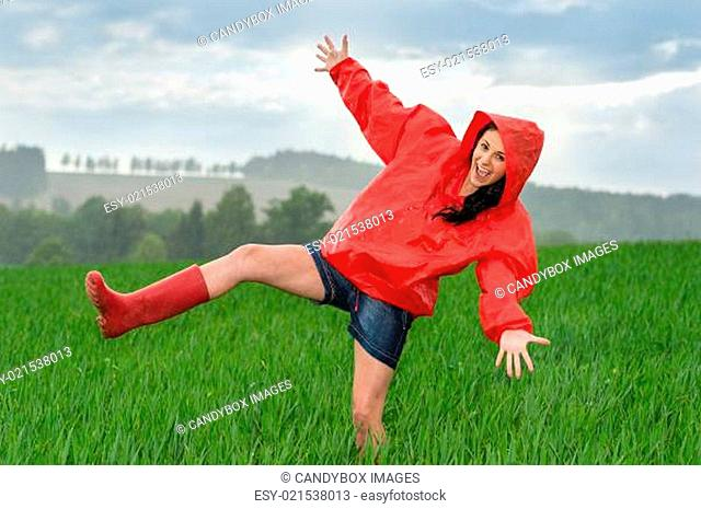 Playful teenage girl dancing in the rain