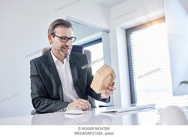 Smiling businessman at desk in office looking at architectural model