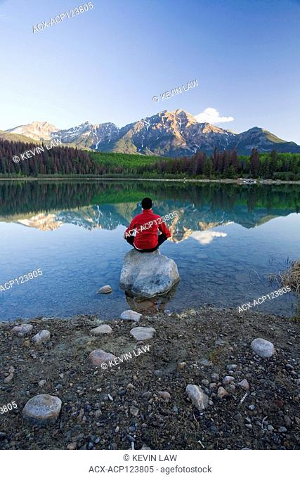Middle age male meditating early morning at Pyramid Lake, Jasper National Park, Alberta, Canada