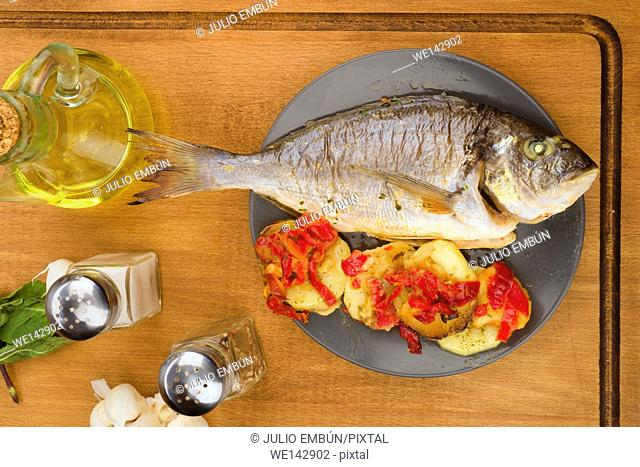 Vertical making roasted sea bream with potatoes on wooden classic