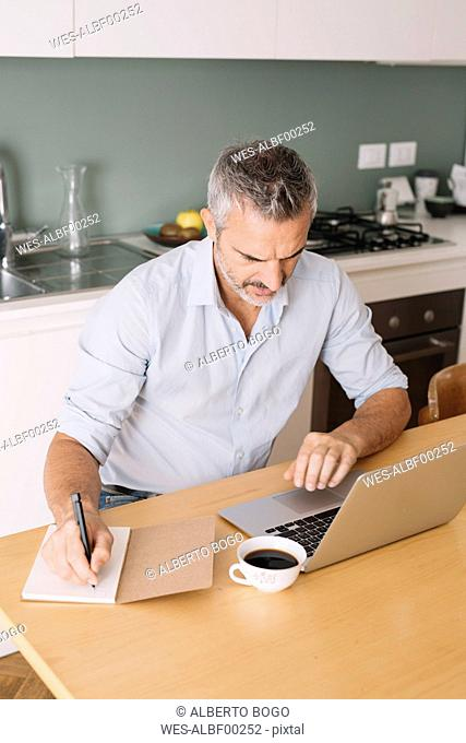 Man writing in notebook and using laptop in home office