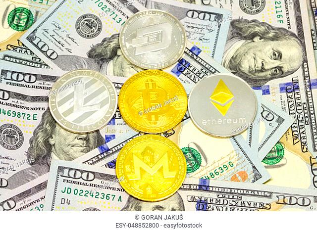 Cryptocurrency coins displayed with bitcoin in the middle on a heap of one hundred dollar bills