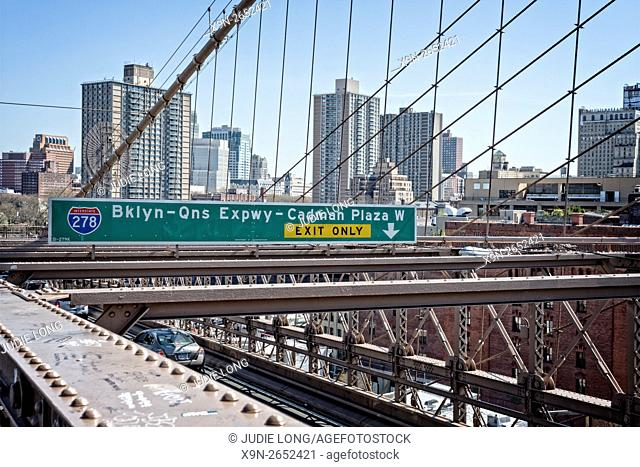 Walking across the Brooklyn Bridge from Manhattan to Brooklyn, passing a diretional sign for traffic on the roadway below