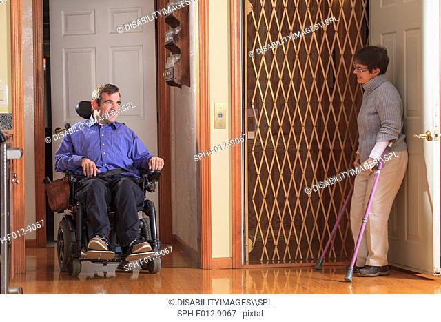 Woman with Cerebral Palsy helping man with Cerebral Palsy in motorized wheelchair into home elevator
