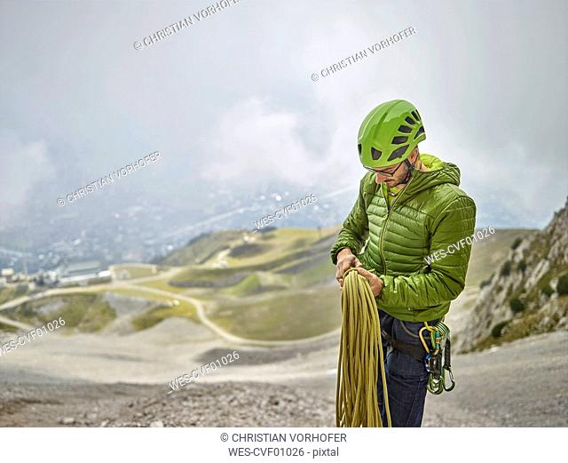 Austria, Innsbruck, Nordkette, man with rope and climbing equipment