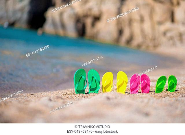 Family flip flops on beach in front of the blue sea