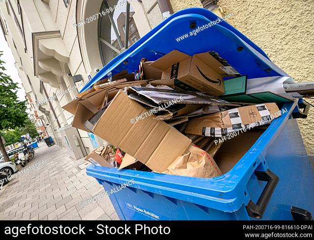 16 July 2020, Bavaria, Munich: An overflowing paper container is waiting in front of a house for collection by the waste collection service