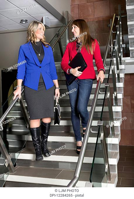 Two professional business women talking on a stairway in an office; St. Albert, Alberta, Canada
