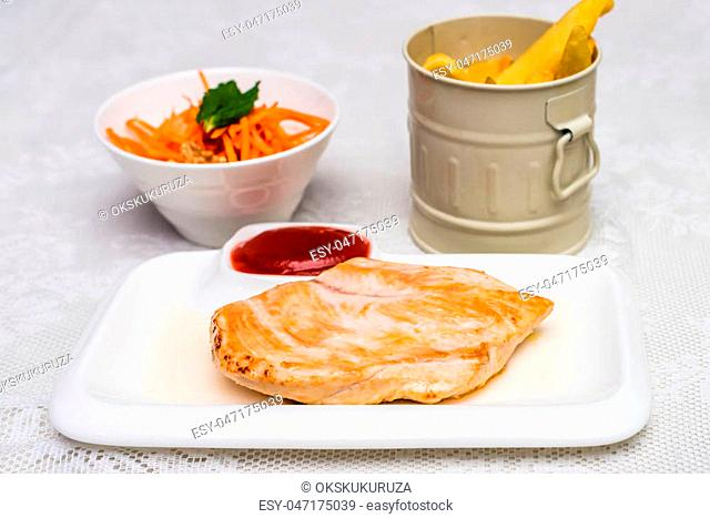 Side view white plate with French fries, chicken meat with carrot salad and sauce
