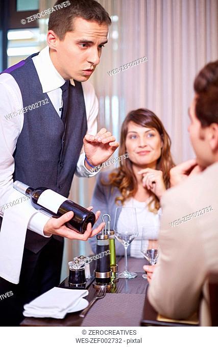 Waiter showing wine bottle to business associates at hotel restaurant