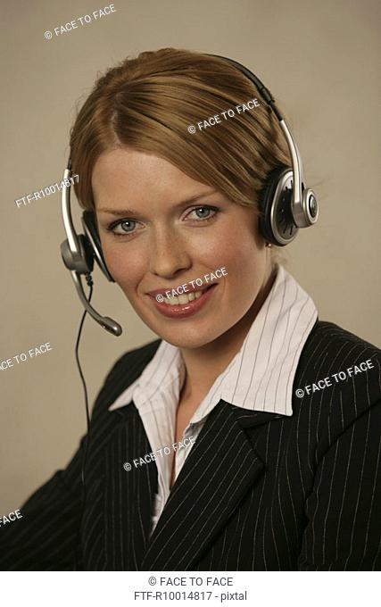 A blonde businesswoman wearing a headphone converses on the mike