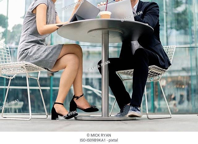 Young businesswoman and man meeting at sidewalk cafe, neck down view